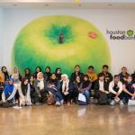 Student volunteers gathered for a photo inside of the Houston Food Bank.