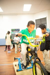 Photo of student using an exercise bike to conduct electricity